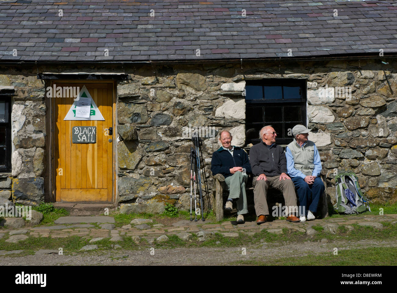 Three senior men sitting outside the Black Sail hut, Ennerdale, Lake District National Park, Cumbria, England UK - Stock Image