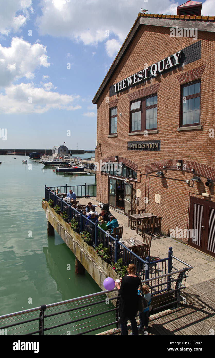 People dining outside a Wetherspoon restaurant at Brighton Marina - Stock Image