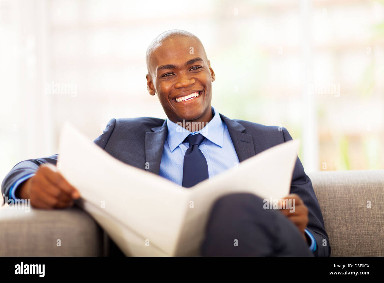african american businessman reading newspaper on sofa - Stock Image