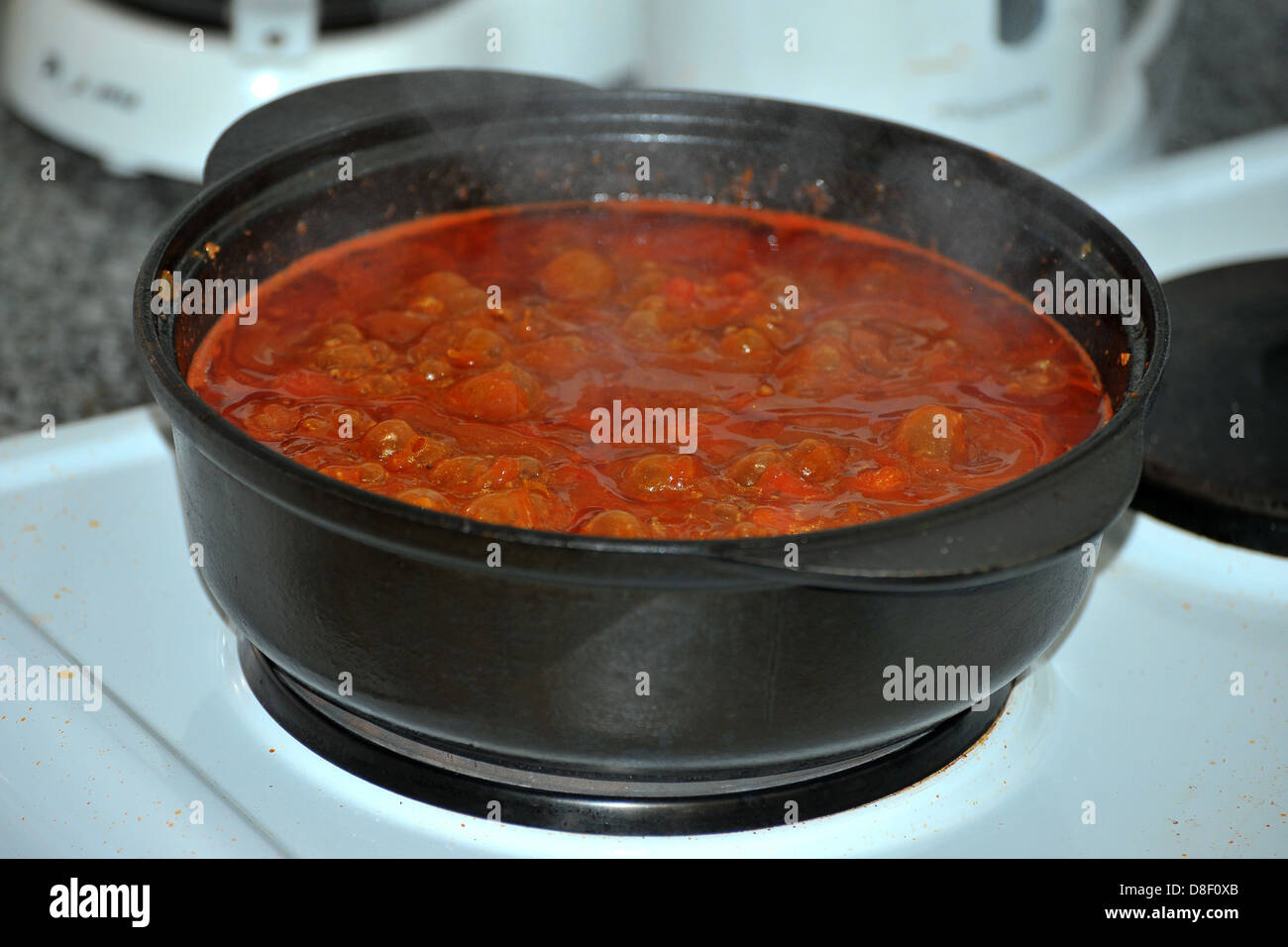 Images of a stew cooking in a cast iron pot on an electric cooker. - Stock Image