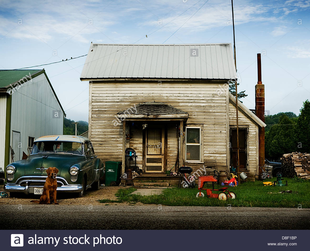 A run down shack in small town America. Old car sets outside a small house with toys and clutter in the yard. - Stock Image