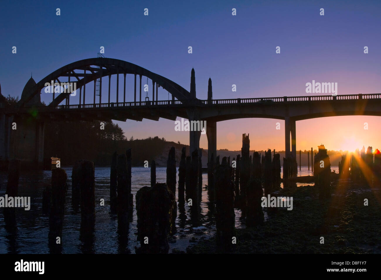 Silhouette of historic coastal bridge at sunset in Florence Oregon USA - Stock Image