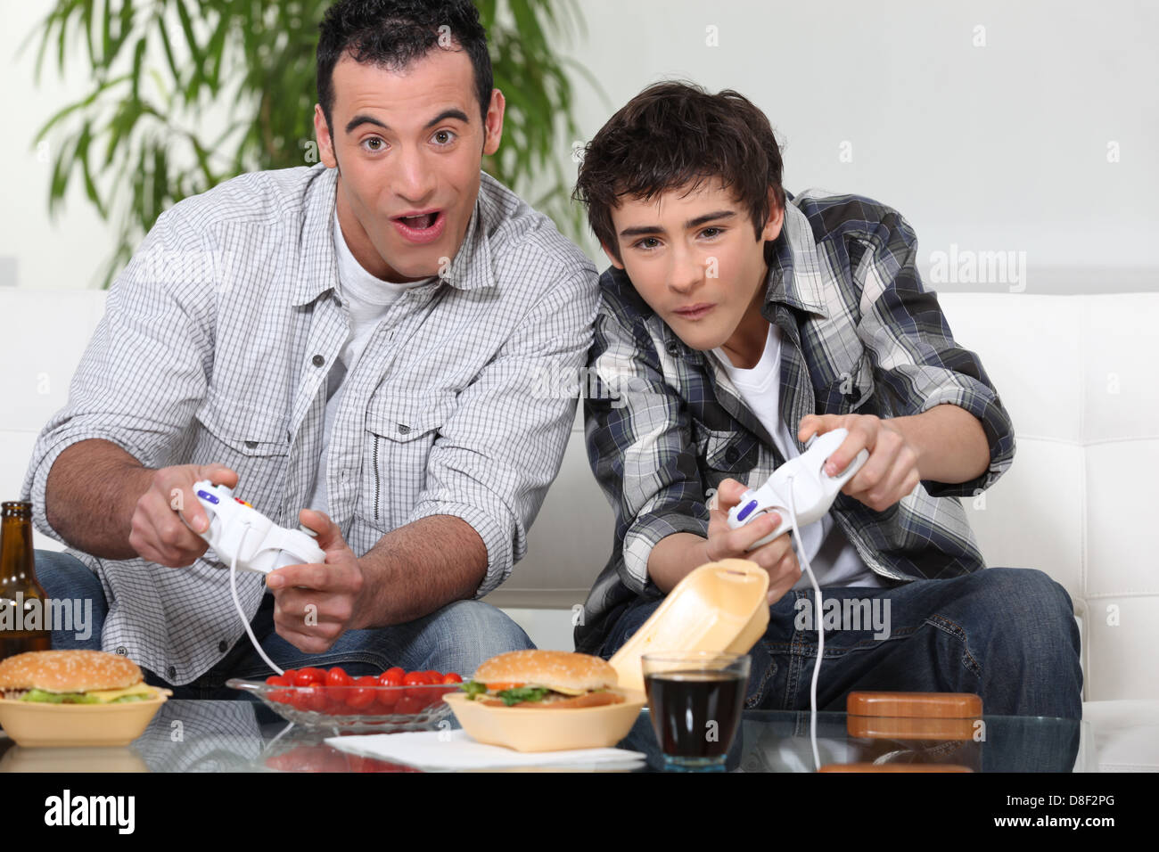 Father and son playing computer games and eating junk food - Stock Image