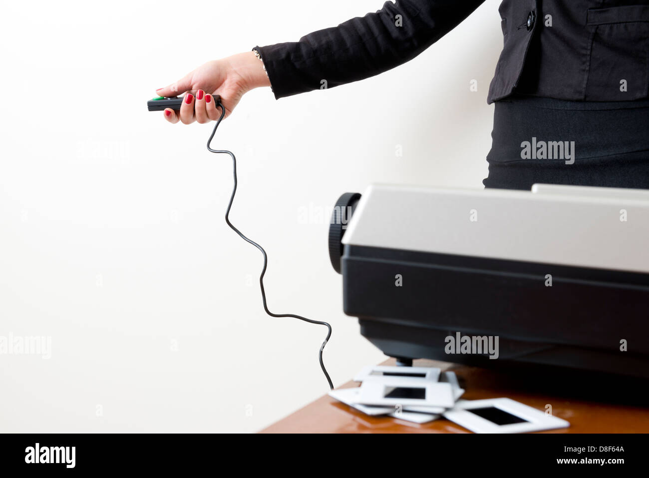 Business woman operating a slide projector against a white wall - Stock Image