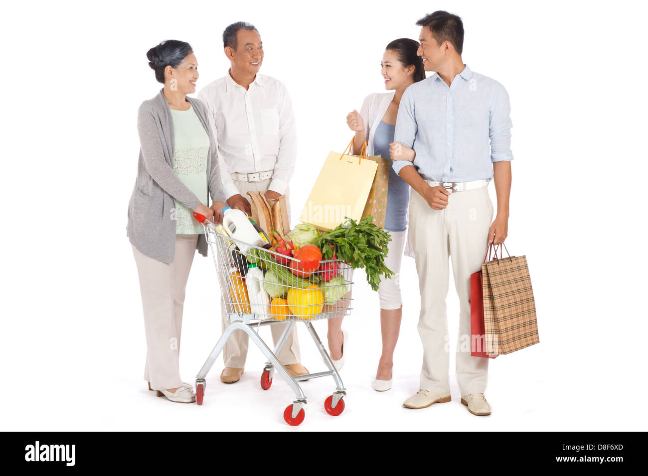 Old couple and young couple shopping with shopping cart - Stock Image