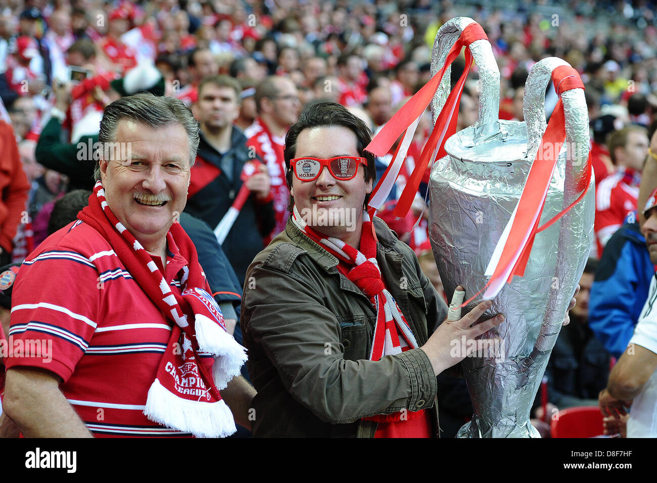Fans of Bayern Munich hold a replicated Champions League trophy in their hands during the Champions League finals - Stock Image