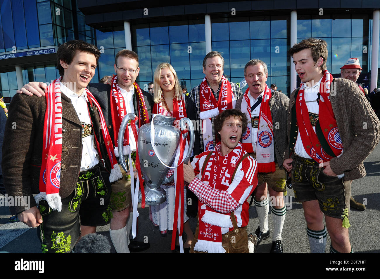 Fans of Bayern Munich hold a replicated Champions League trophy in their hands as they sing a song after the Champions - Stock Image