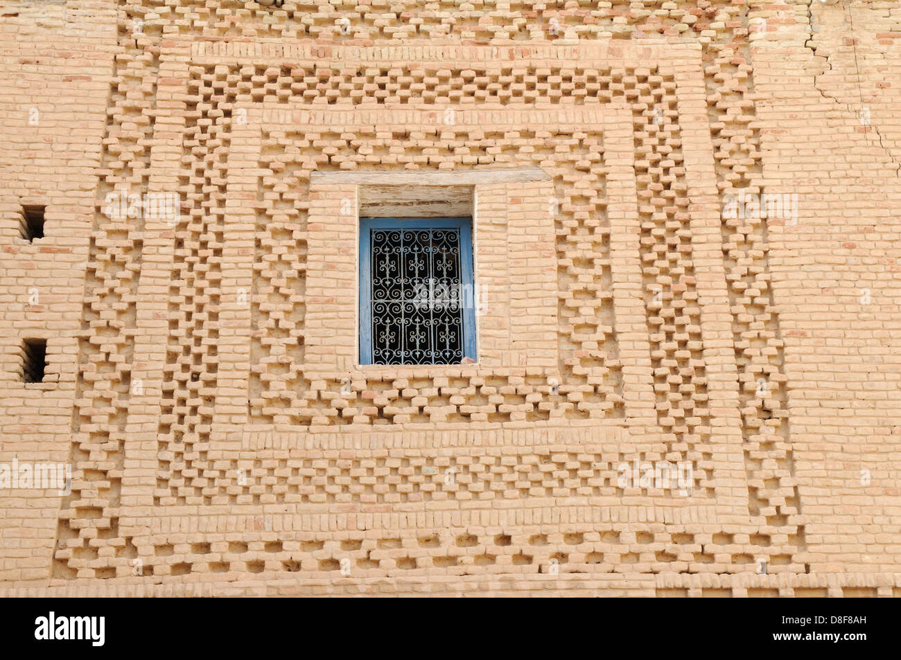 A blue painted window surrounded by an decorative pattern of air dried bricks in the old Medina Tozeur Tunisia - Stock Image