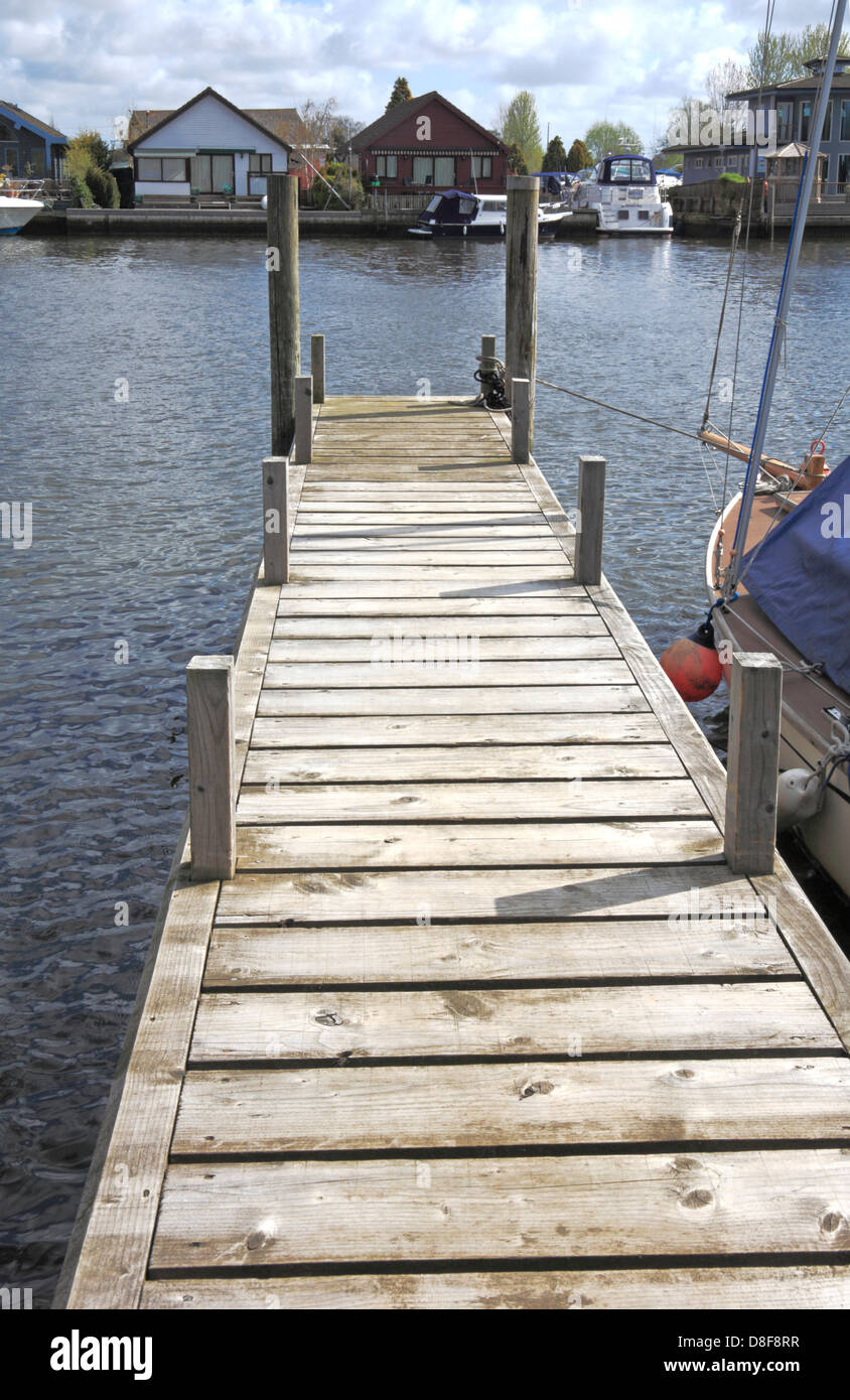 A view of a landing stage extending into the River Yare on the Norfolk Broads at Coldham Hall, Norfolk, England, - Stock Image
