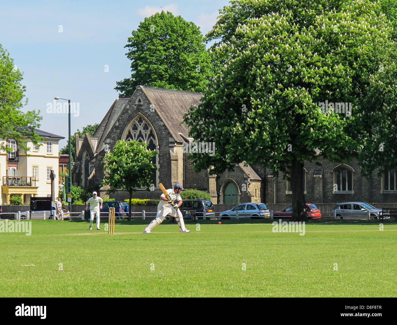 Batsman hits ball as cricket is played on Twickenham Green in Summer - Stock Image