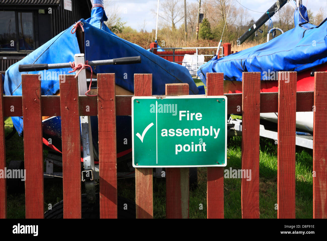 A Fire Assembly Point notice outside a Norfolk Broads Sailing Club. - Stock Image