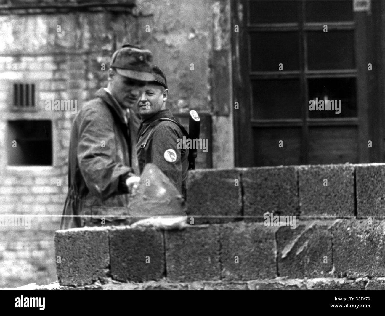 Unter der Aufsicht eines bewaffneten Volkspolizisten errichtet ein Ostberliner Bauarbeiter am 18.8.1961 an der sowjetisch - Stock Image