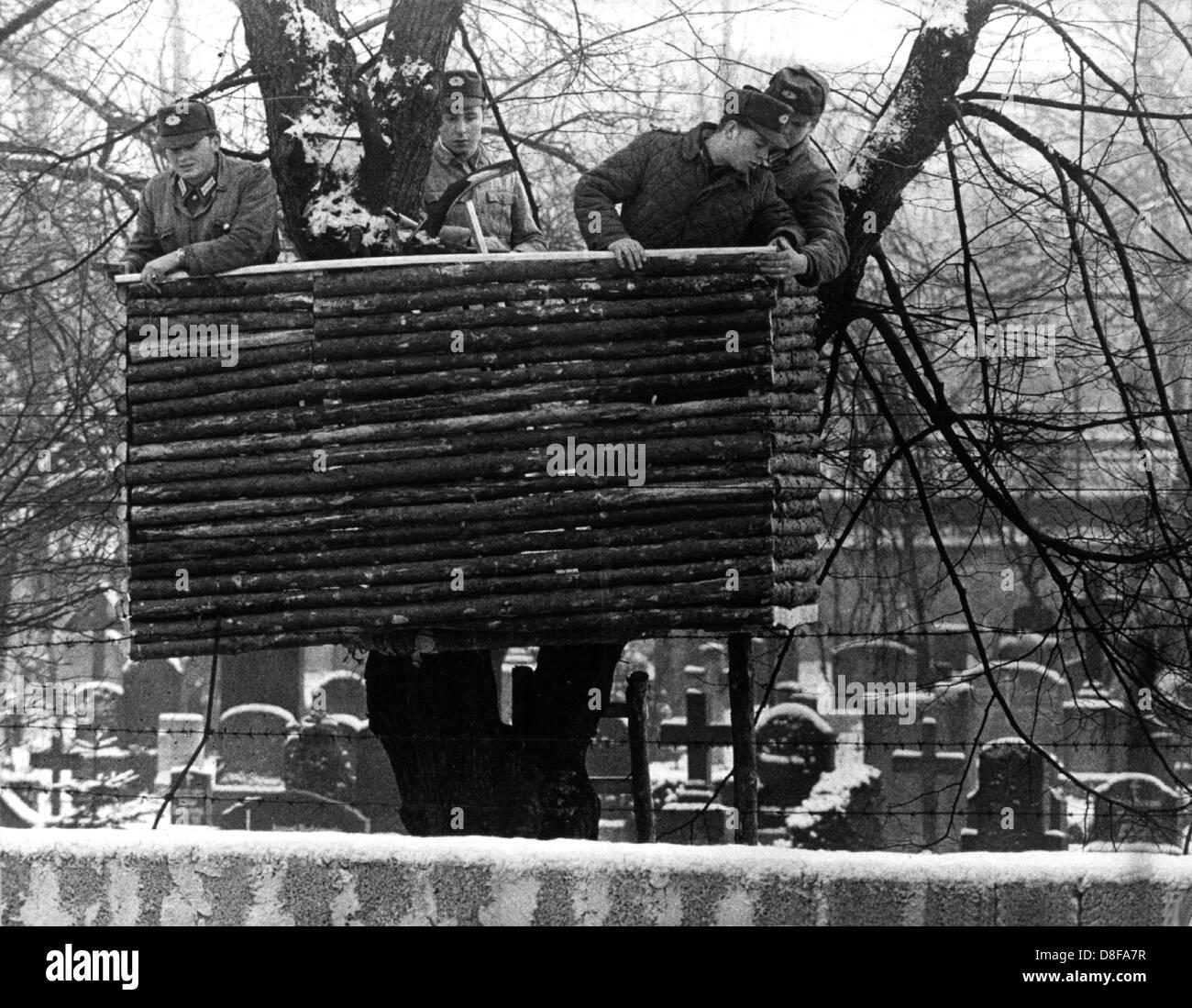Auf dem Friedhof der St. Hedwigs-Domgemeinde in der Liesenstraße an der Grenze zum Westberliner Bezirk Wedding sind Volkspolizisten dabei, in einem Baum zwischen den Gräbern hinter der vier Meter hohen Sperrmauer einen Beobachtungsstand zu errichten. Aufgenommen 1961. Stock Photo