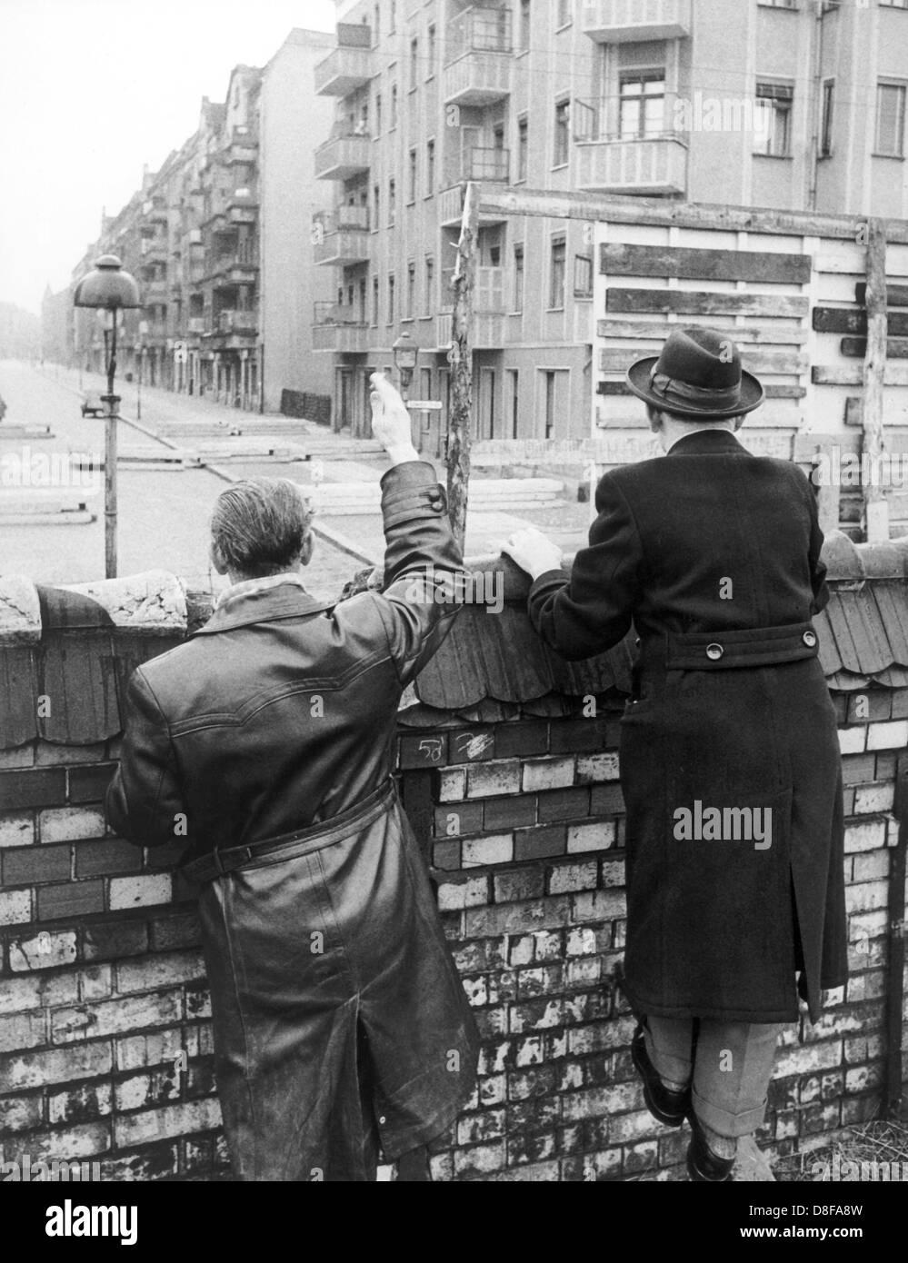 Westberliner Männer winken, solange die Möglichkeit noch besteht, im Jahr 1962 ihren Verwandten und Bekannten in Ostberlin zu. Volkspolizisten der DDR sind damit beschäftigt, eine Sichtblende zu errichten. Am frühen Sonntagmorgen des 13. August 1961 wurde unter der Aufsicht von bewaffneten Streitkräften der DDR mit der Errichtung von Straßensperren aus Stacheldraht und dem Bau einer Mauer begonnen, um den Ostteil Berlins vom Westteil abzusperren. Die Mauer sollte den ständig steigenden Flüchtlingsstrom von Ost- nach West-Berlin stoppen. +++(c) dpa - Report+++ Stock Photo