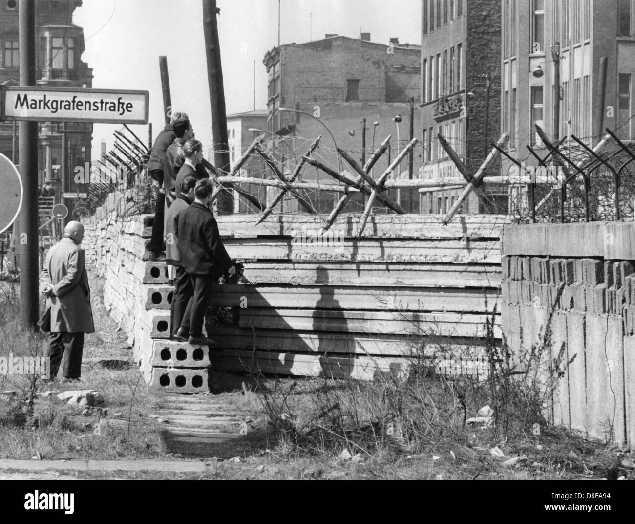 Westberliner Männer werfen am 17.04.1964 einen Blick über die im Bau befindliche vorverlegte Mauer an der Markgrafenstraße in Berlin. Am frühen Sonntagmorgen des 13. August 1961 wurde unter der Aufsicht von bewaffneten Streitkräften der DDR mit der Errichtung von Straßensperren aus Stacheldraht und dem Bau einer Mauer begonnen, um den Ostteil Berlins vom Westteil abzusperren. Die Mauer sollte den ständig steigenden Flüchtlingsstrom von Ost- nach West-Berlin stoppen. +++(c) dpa - Report+++ Stock Photo
