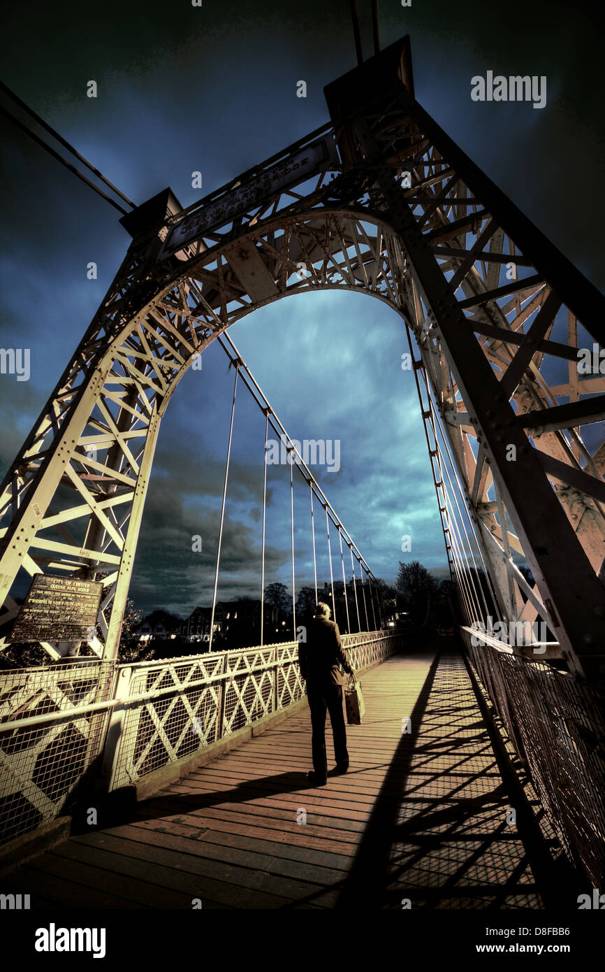 Man crossing the River Dee bridge at Chester with his briefcase , on his way home in the evening - Stock Image