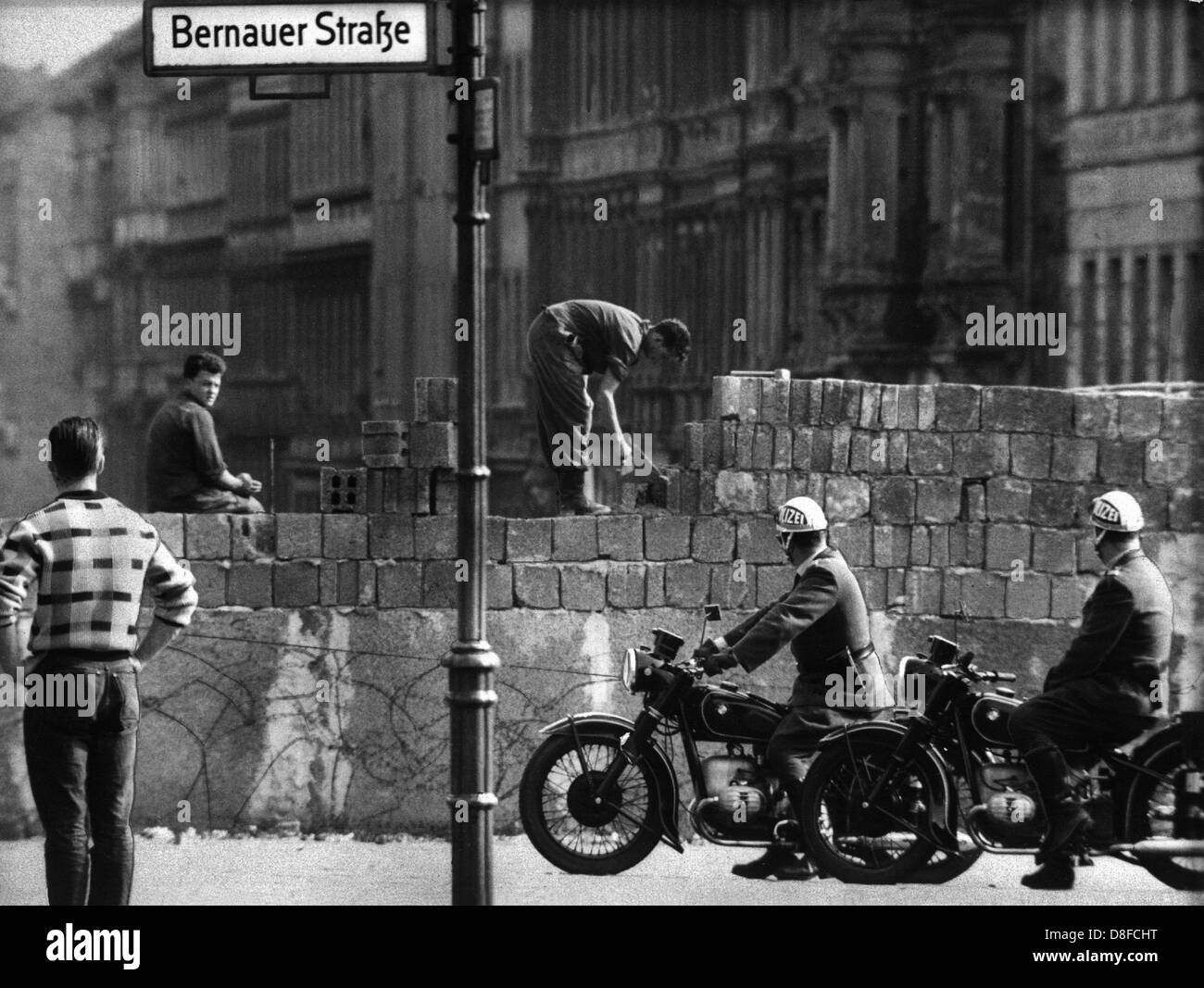 Workers add layers of brick to the Berlin Wall on Bernauer Strasse where critical incidents had occurred almost - Stock Image