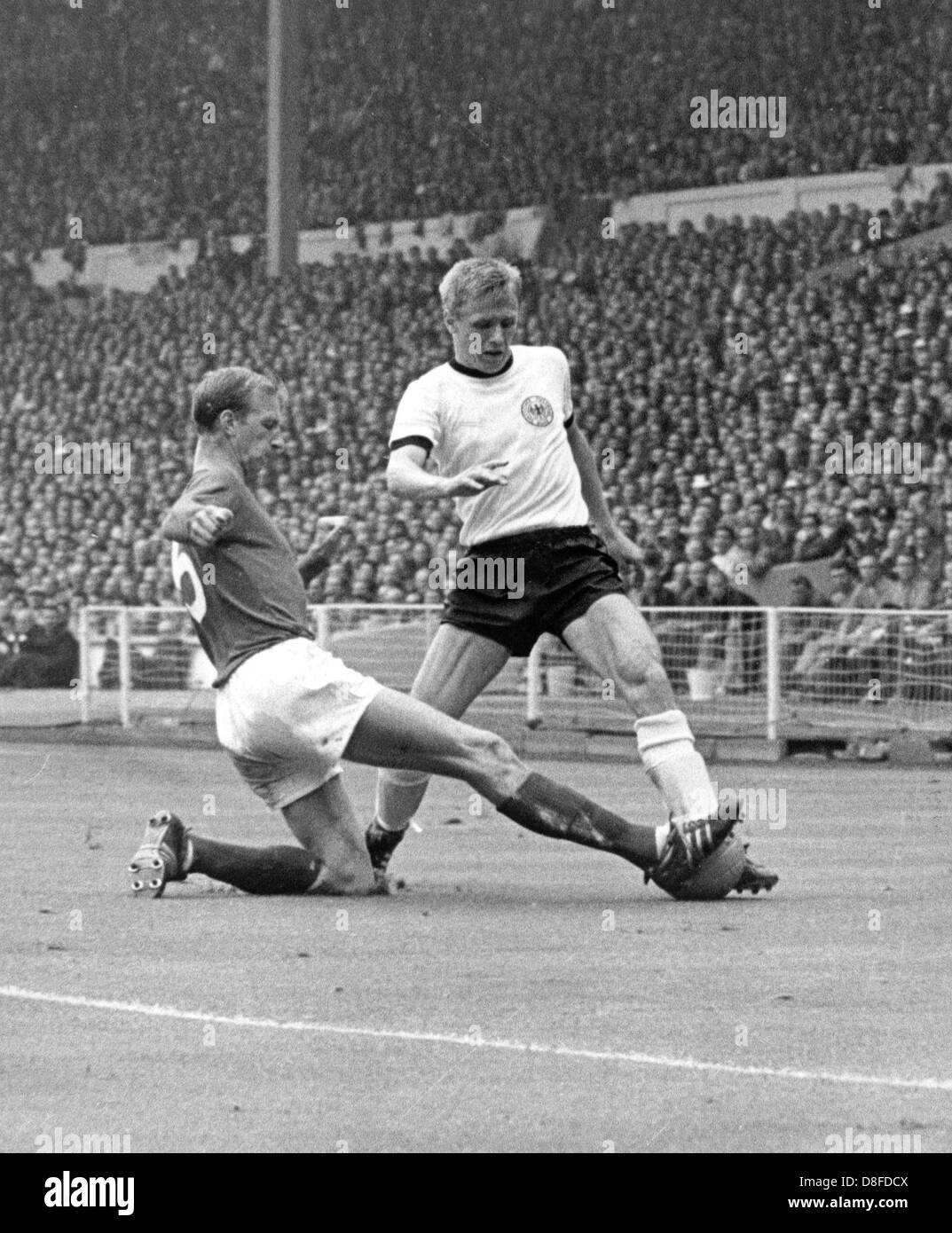 English defender Jack Charlton (L) stretches his leg and stops the approach of German forward Siegfried Held (R) Stock Photo