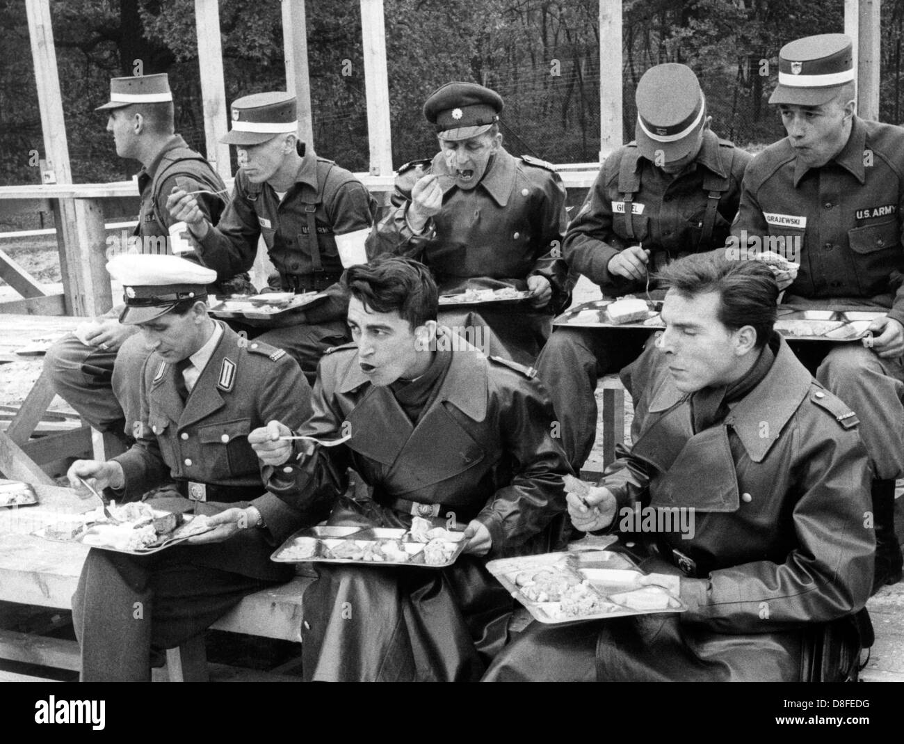 Soldiers of the US army have their meal together with police men of West Berlin shortly before the beginning of the field exercise on the 23rd of October in 1962 on the US artillerey range Keerans Range in Grunewald in Berlin. The exercise was part of a four day manoeuvre of the US troops. Stock Photo