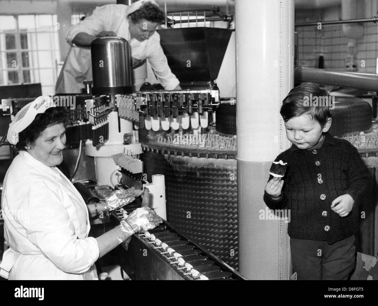 A little boy wonders about the machine which continuously produces ice cream on the 10th of February in 1967. Stock Photo