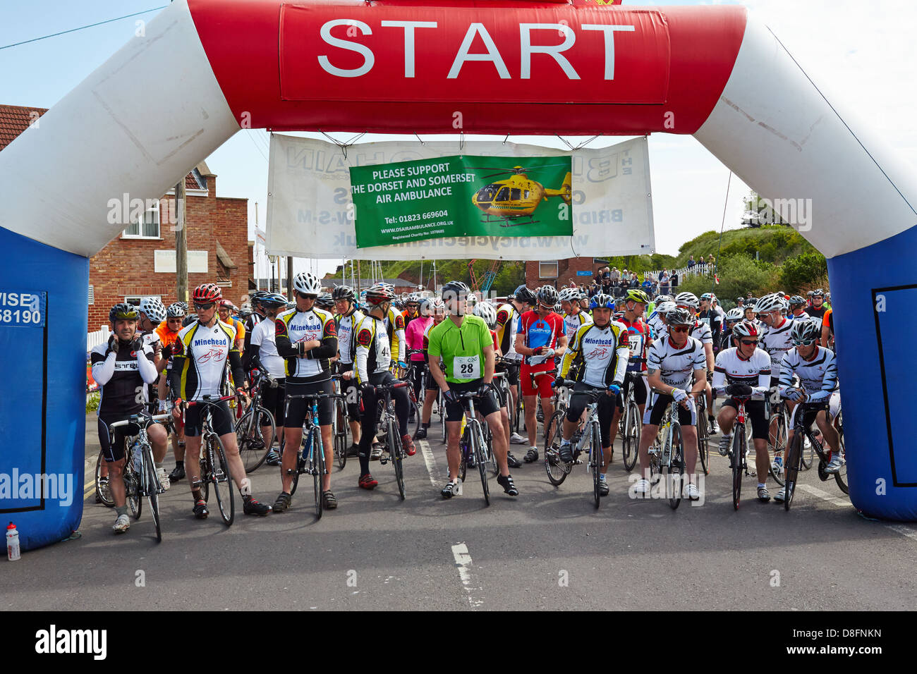 Cyclists lineup for the start of the Coast to Coast Cycle Challenge 2013 from Watchet in Somerset to Bridport in - Stock Image