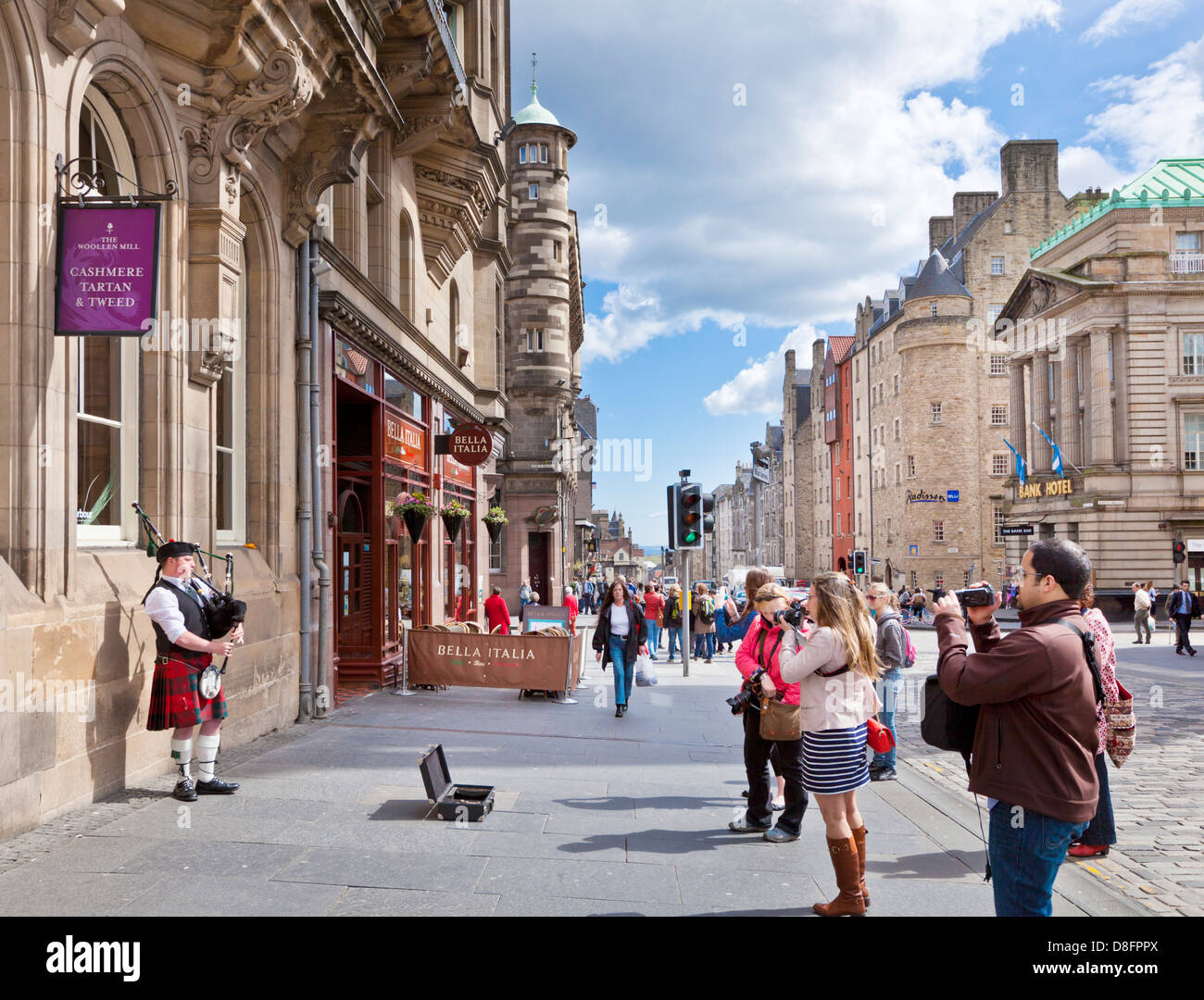 Tourists watching a piper playing on the  High Street in Edinburgh old town the royal Mile Midlothian Scotland UK - Stock Image