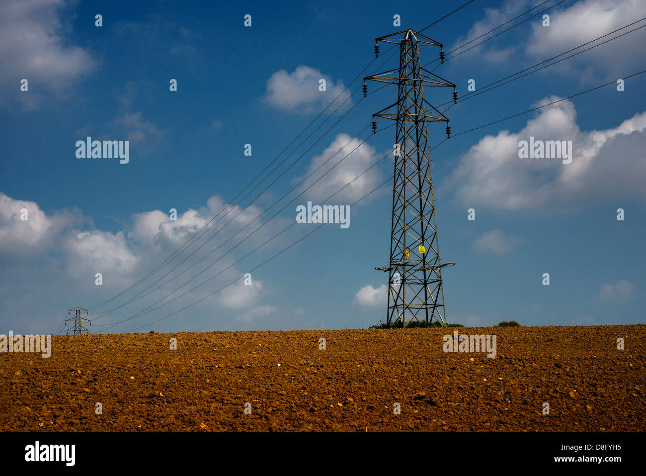 Powerlines stretch across East Sussex farmland. - Stock Image