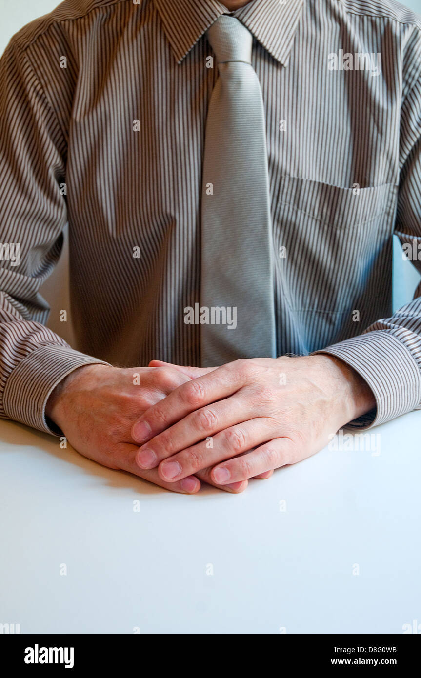 Executive sitting, hand on hand. Close view. - Stock Image