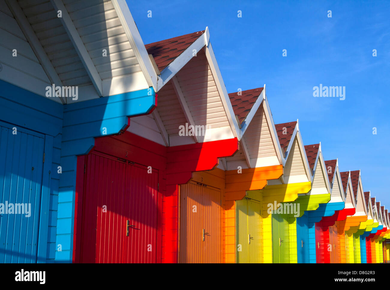 Brightly coloured wooden beach huts, known as beach chalets, in sunshine at Scarborough North Bay, North Yorkshire, - Stock Image