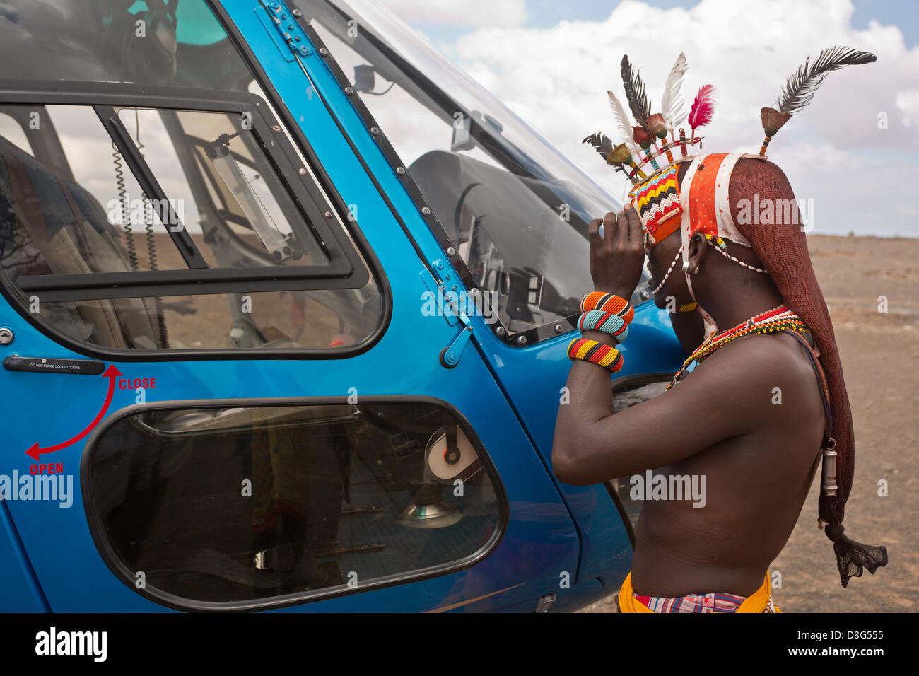 Rendille man looking through helicopter's front window.Kenya - Stock Image
