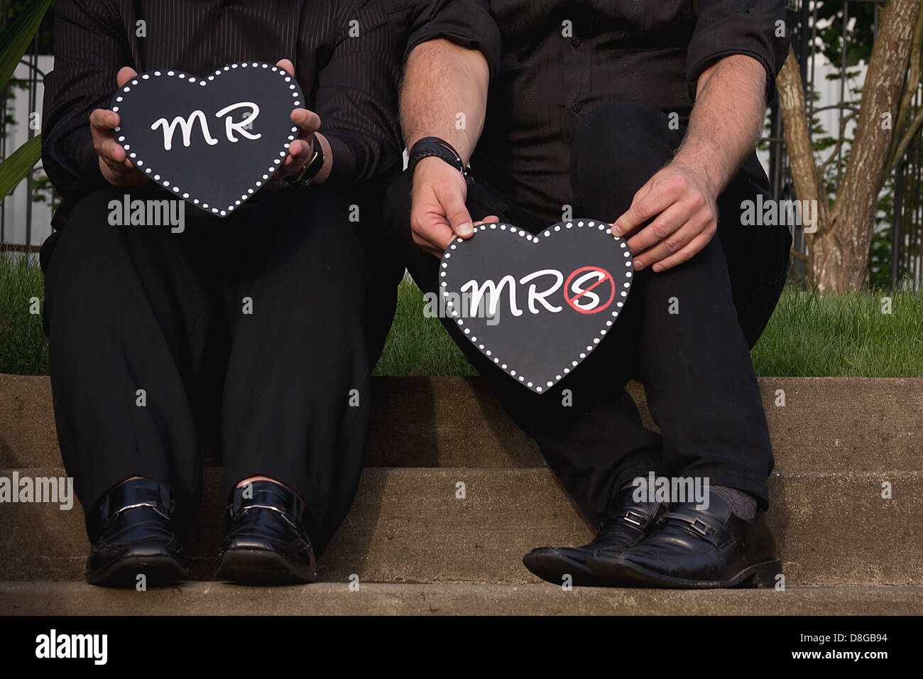 Homosexual couple holding Mr and Mrs heart-shaped signs. - Stock Image