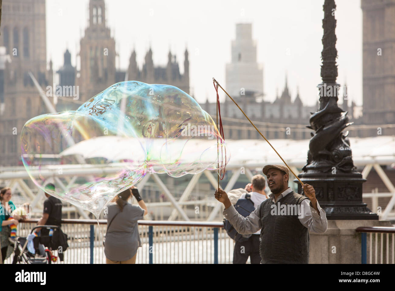 Children chasing bubbles made by a street entertainer on London's South Bank. - Stock Image