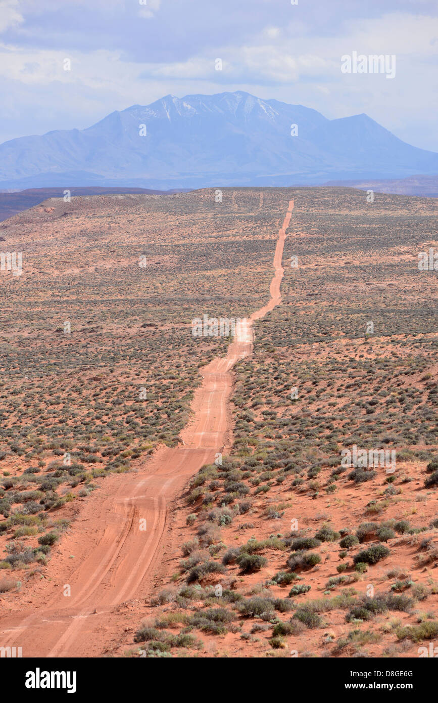 Dirt road in the Burr Desert of Southern Utah. The Henry Mountains are in the background. - Stock Image