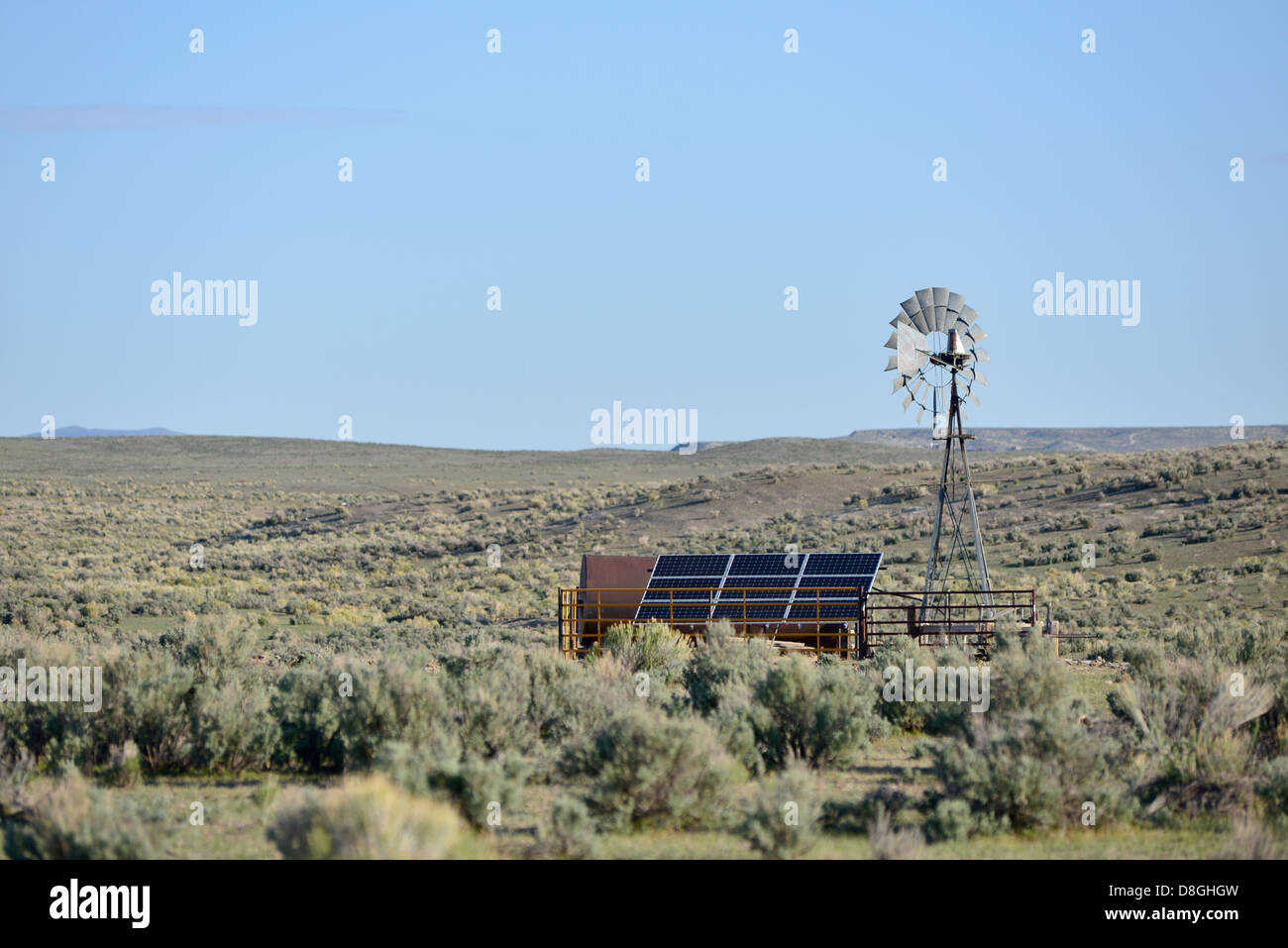Wind pump and solar panels at a water tank in the Nevada desert. - Stock Image