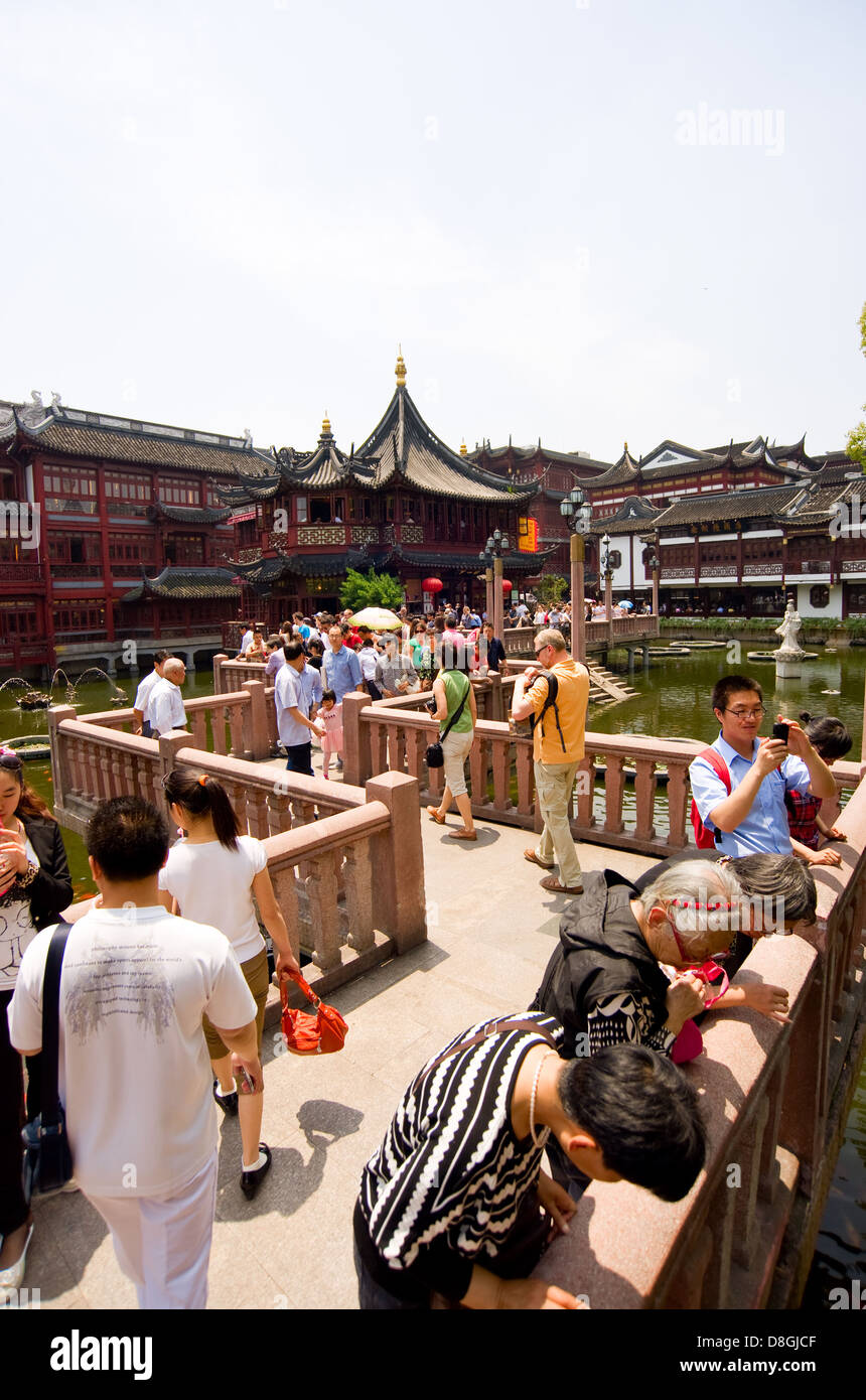 Tourists walk along the Bridge of Nine Turnings in the Old Town of Shanghai, China. - Stock Image