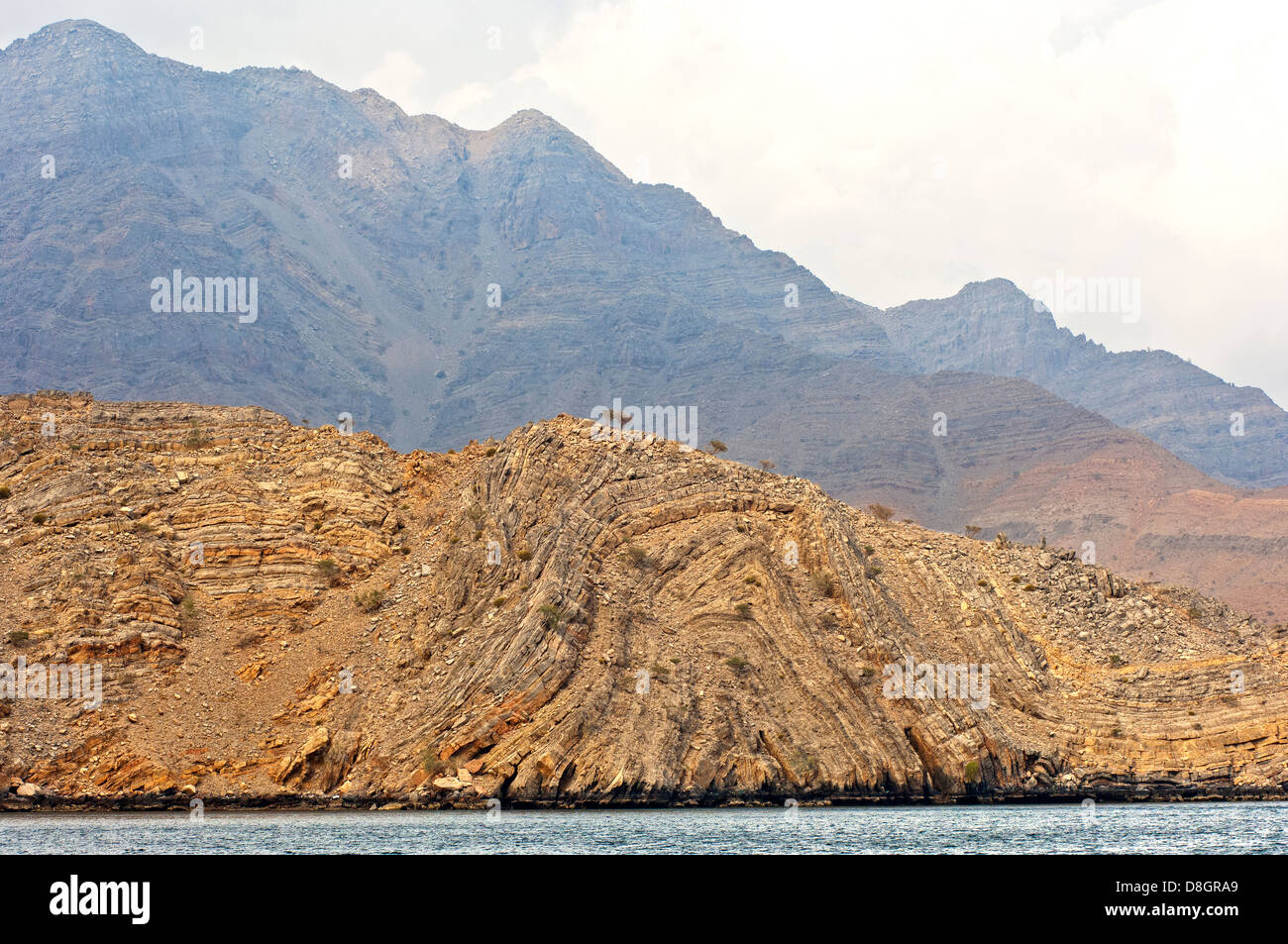 Geological folds in rock faces surrounding the Khor Ash Sham Fjord, Musandam, Sultanate of Oman - Stock Image