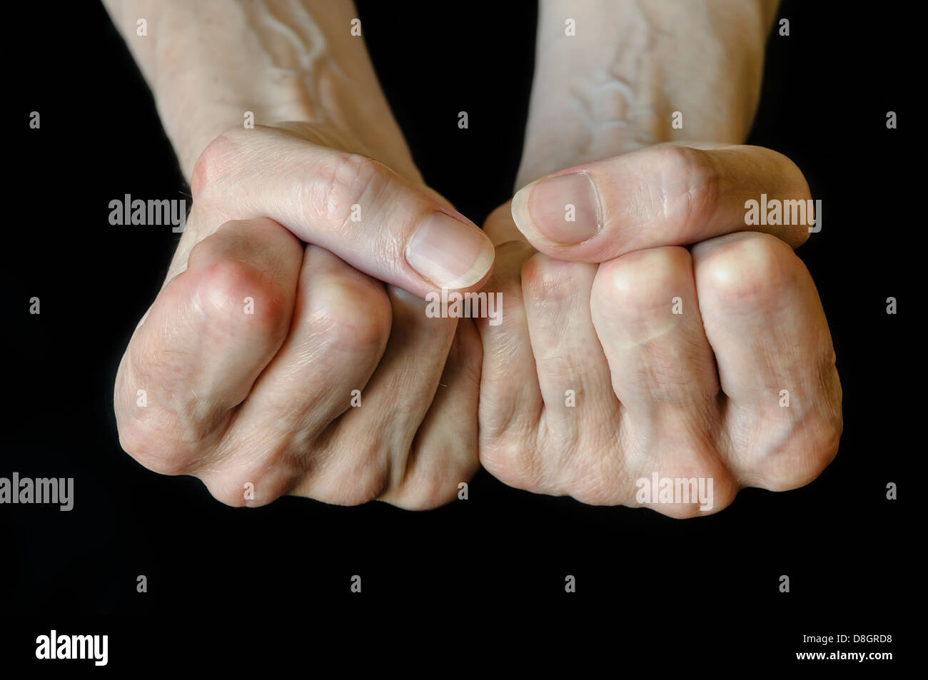 Senior woman showing fists on black background - Stock Image