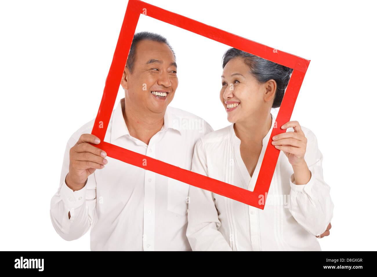 Old couple holding photo frame Stock Photo