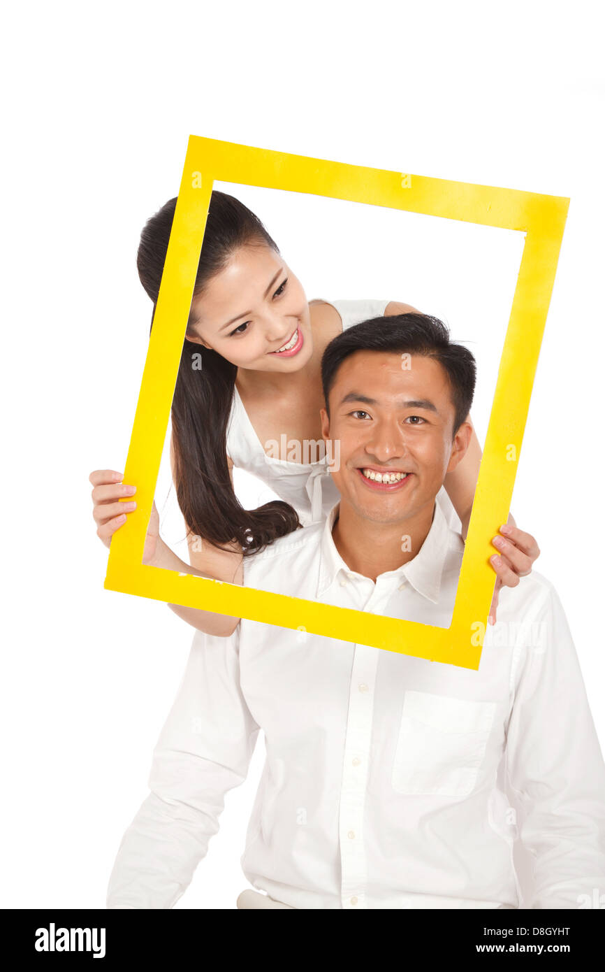 Young couple holding photo frame Stock Photo