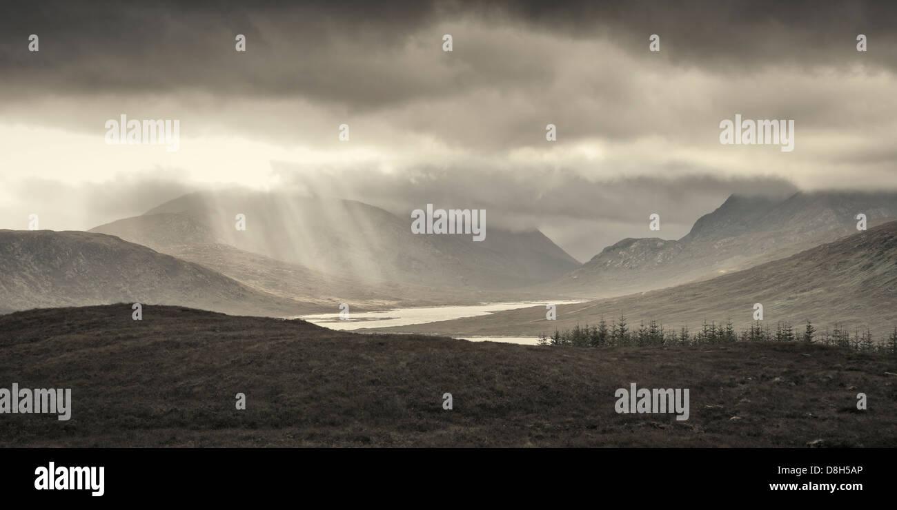 Sun rays pass through cloud cover, Highlands, Scotland, United Kingdom - Stock Image