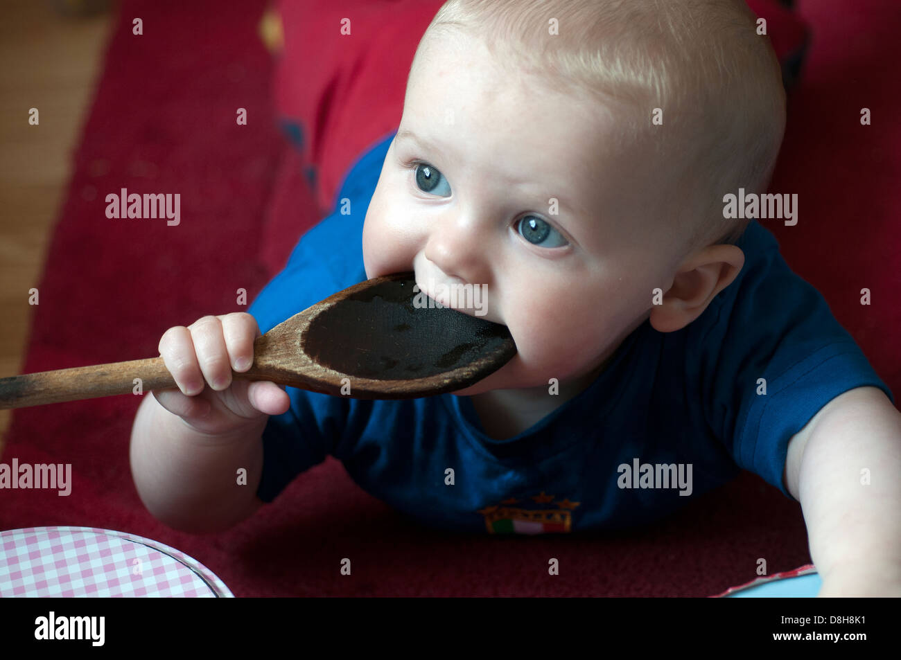 baby teething on yummy spoon,wooden spoon,fang, denticulation tusk denticle dentition - Stock Image