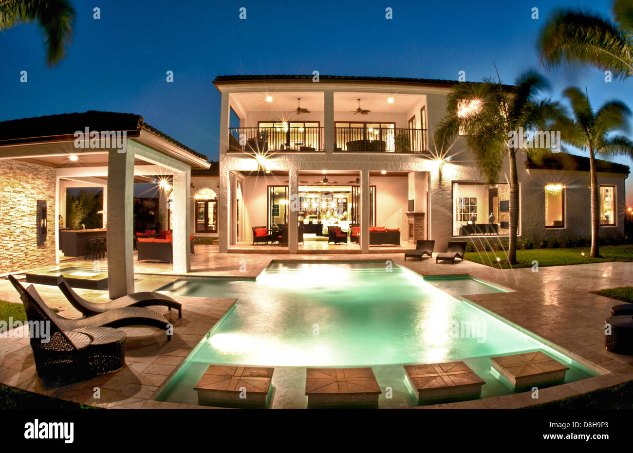 Luxury Home Worth Several Million Dollars Pool At Twilight With Palm Trees  And Blue Sky