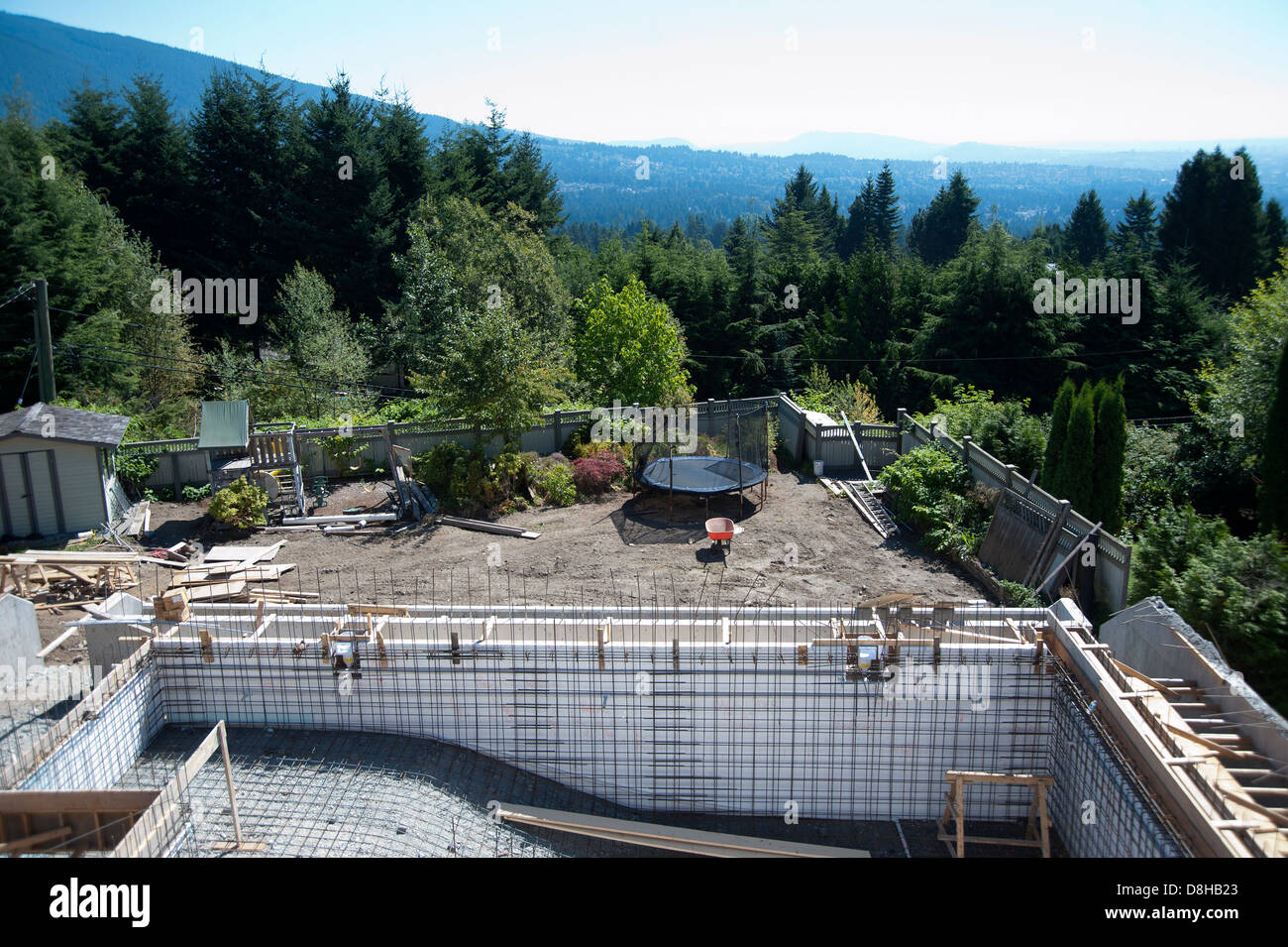 Construction for a  backyard swimming pool being built in West Vancouver, British Columbia, Canada - Stock Image