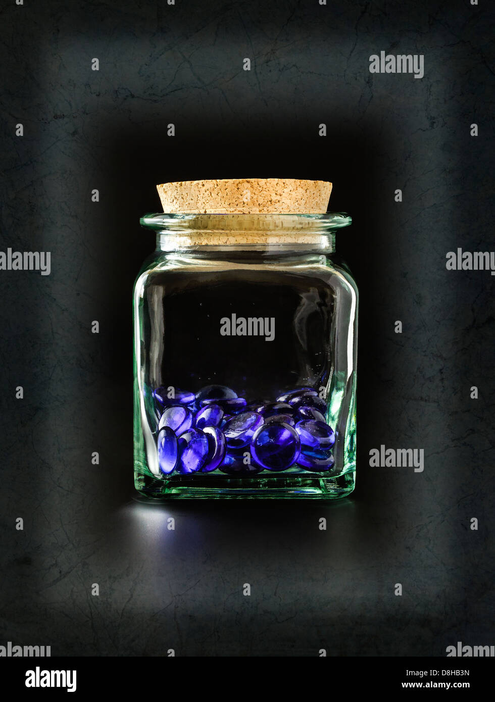 Decorative blue glass stones in glass container - Stock Image