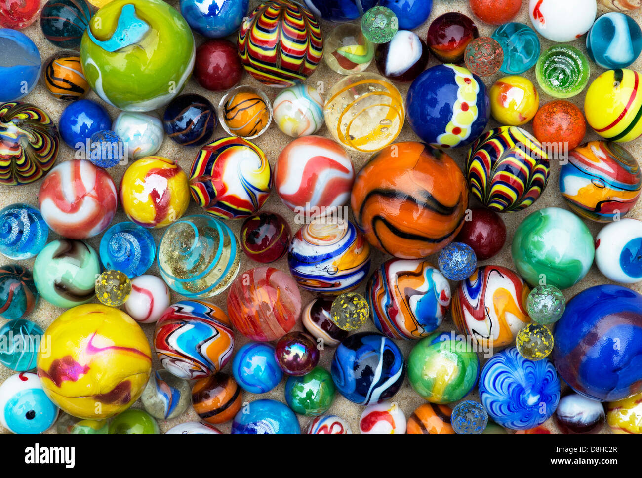 Colourful marbles on sand pattern - Stock Image