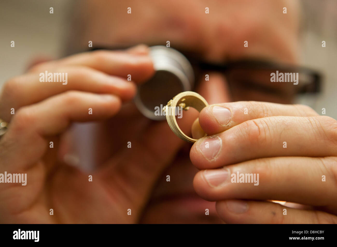 Examining the hallmark on a gold ring at the London Assay Office in Gutter Lane Photo Credit: David Levenson - Stock Image