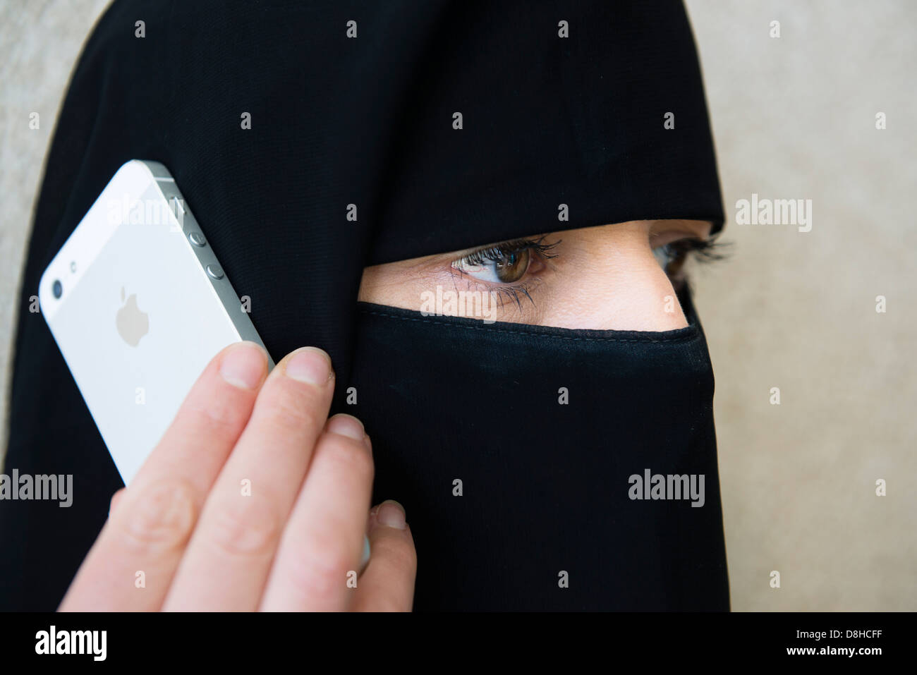 Arab woman wearing traditional black niqab face covering using iPhone 5 to make call - Stock Image