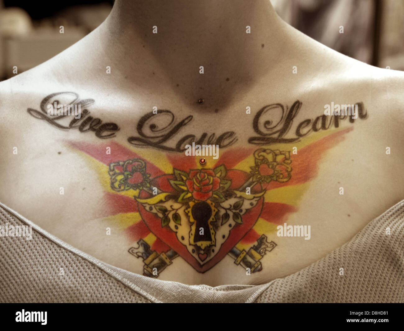 Live Love Learn Tattoo with a keyhole heart on a womans chest - Stock Image