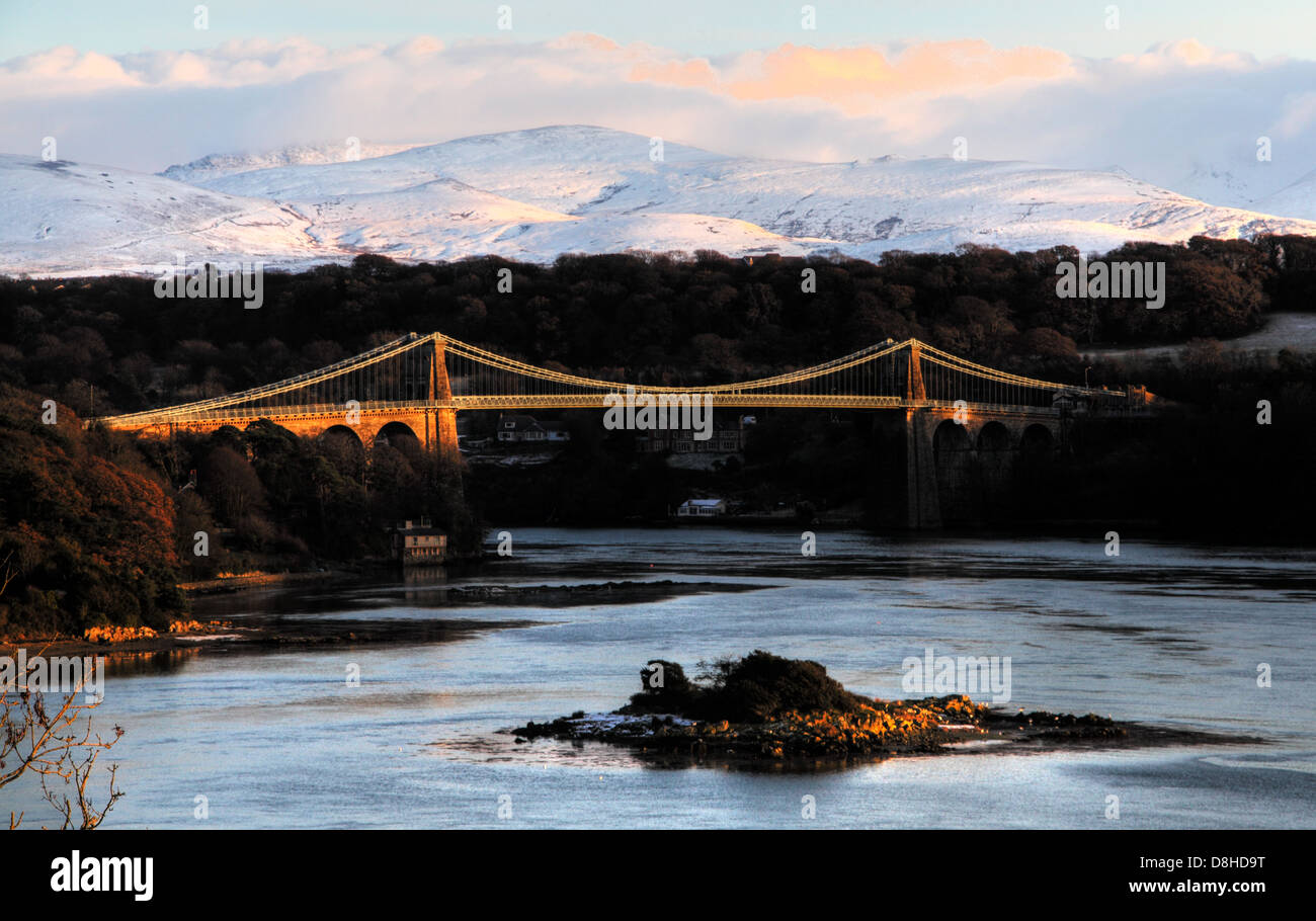 The Menai Suspension Bridge, built in 1826 by Thomas Telford, at sunset with snow covered mountains of Snowdonia - Stock Image