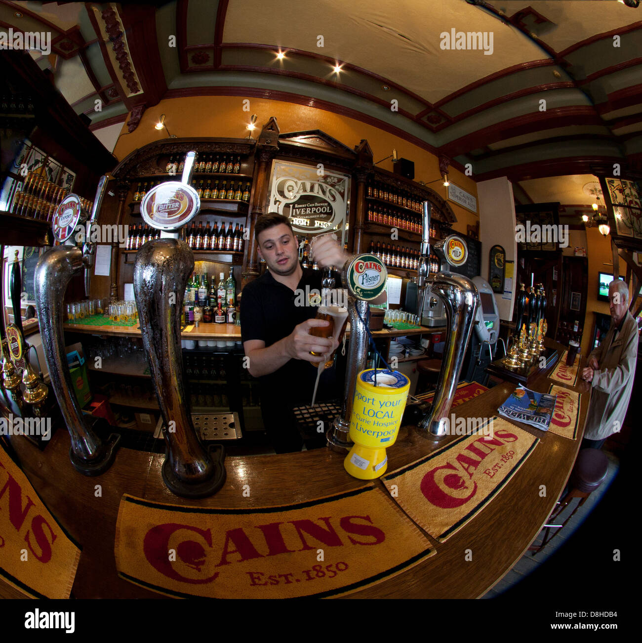 Fisheye shot of Cains Brewery Tap Liverpool , Pulling a pint of English ale - Stock Image